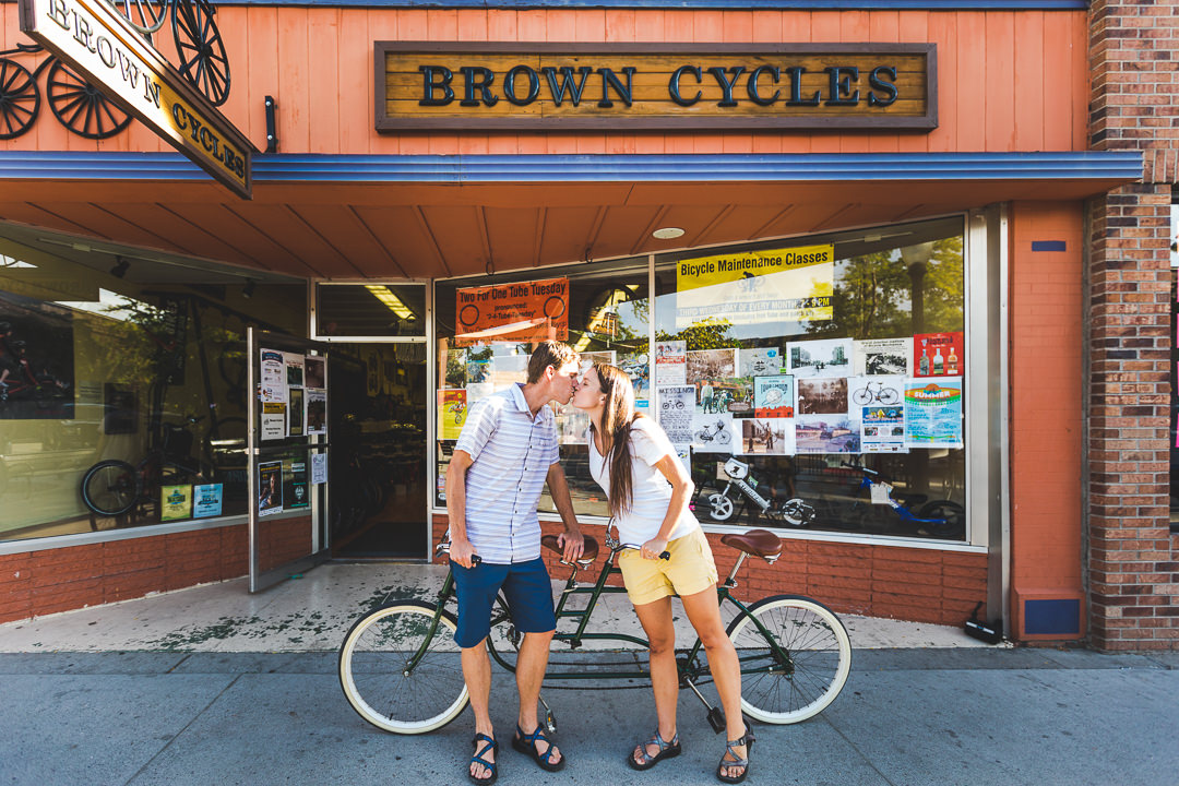 Engaged couple in casual attire kissing while leaning against tandem bike in front of bike shop
