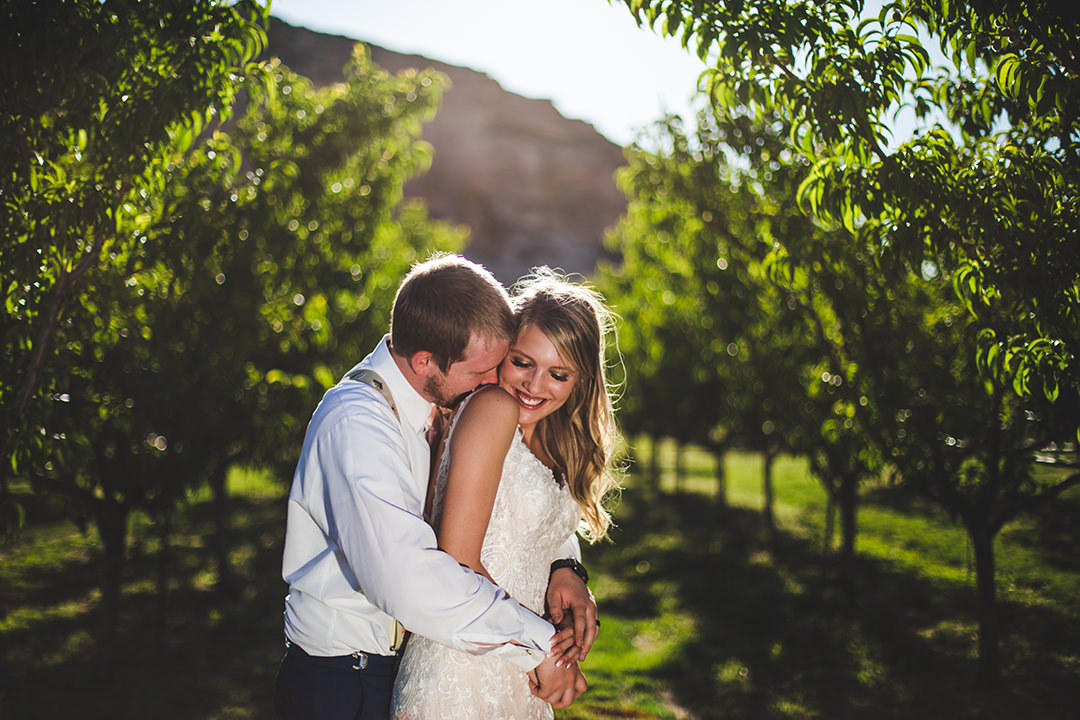 Groom kisses the shoulder of bride from behind in Colorado peach orchard