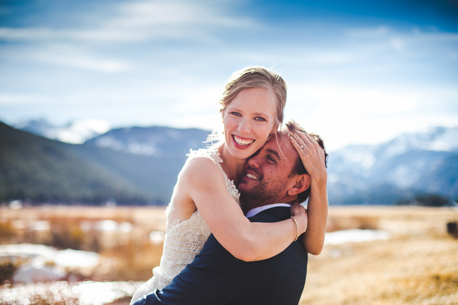 Bride hugs her groom as he picks her up with the rocky mountains behind them