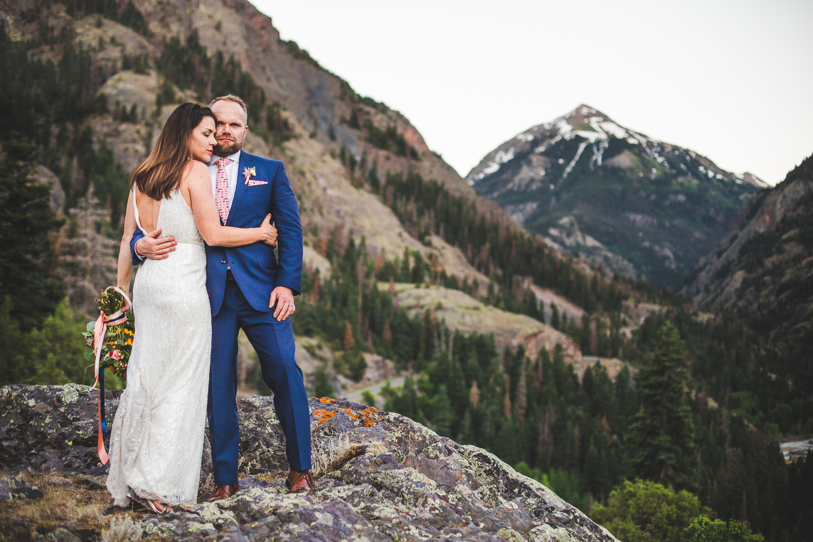 Bride hugs groom from the side with the San Juan Mountains of Colorado behind them