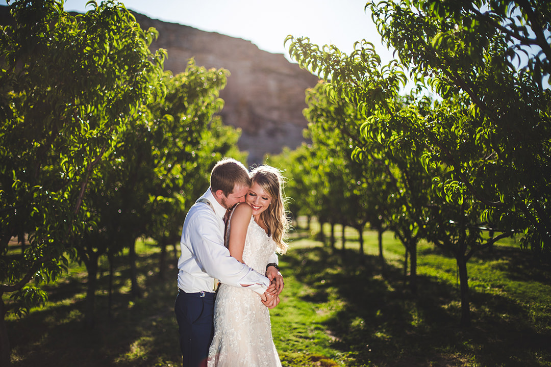 Groom hugging his laughing bride in a peach orchard
