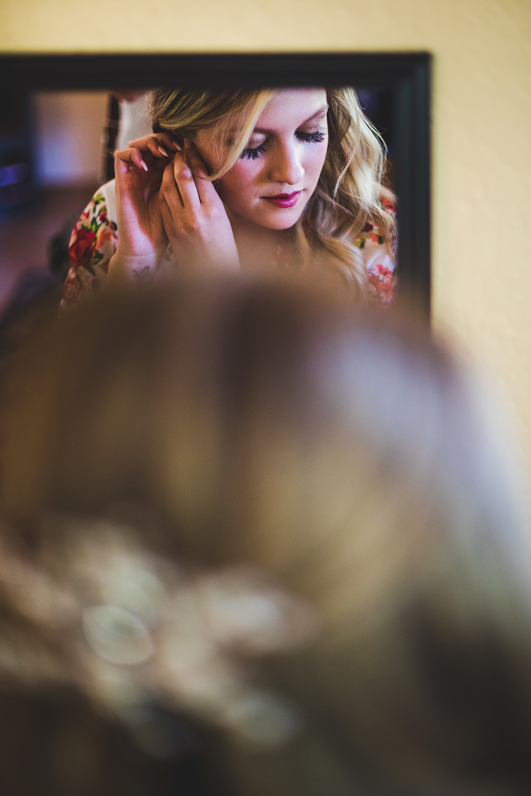 Bride putting on earrings reflected in the mirror