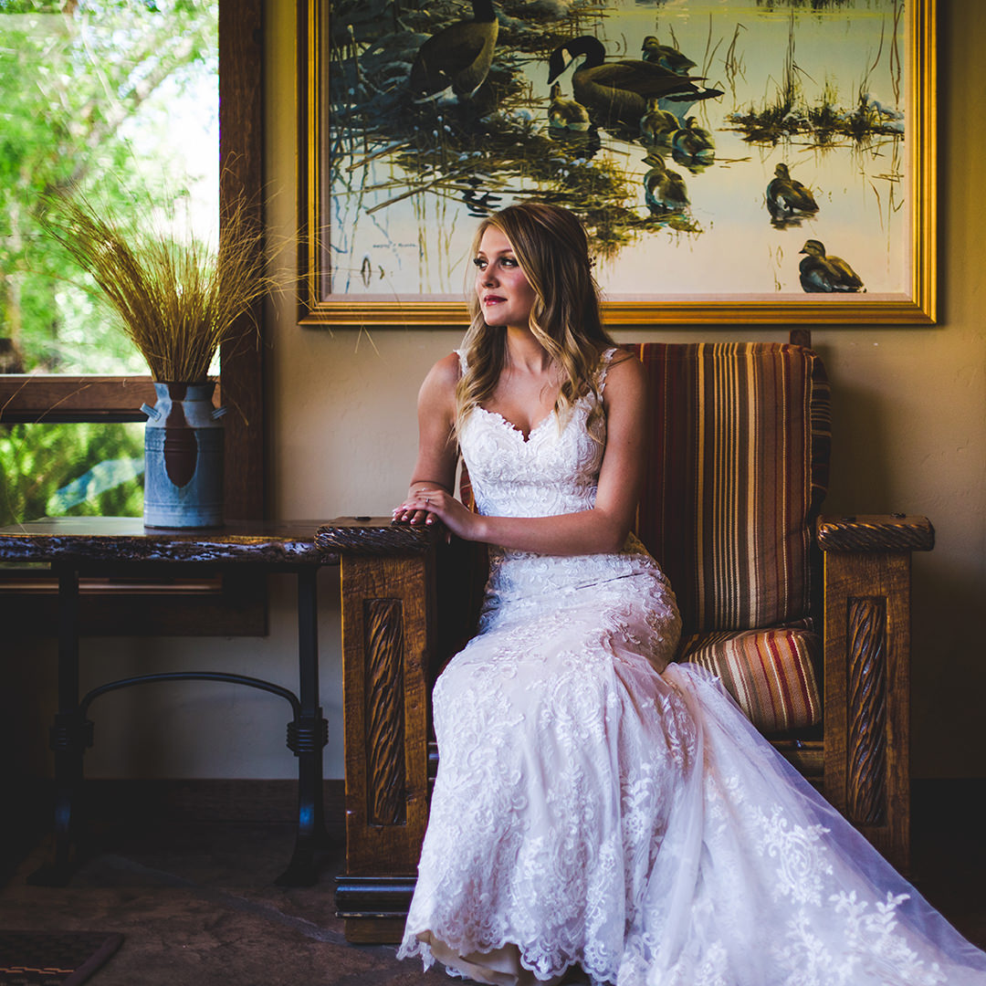 Bride looking out to her wedding site while sitting on an elegant chair