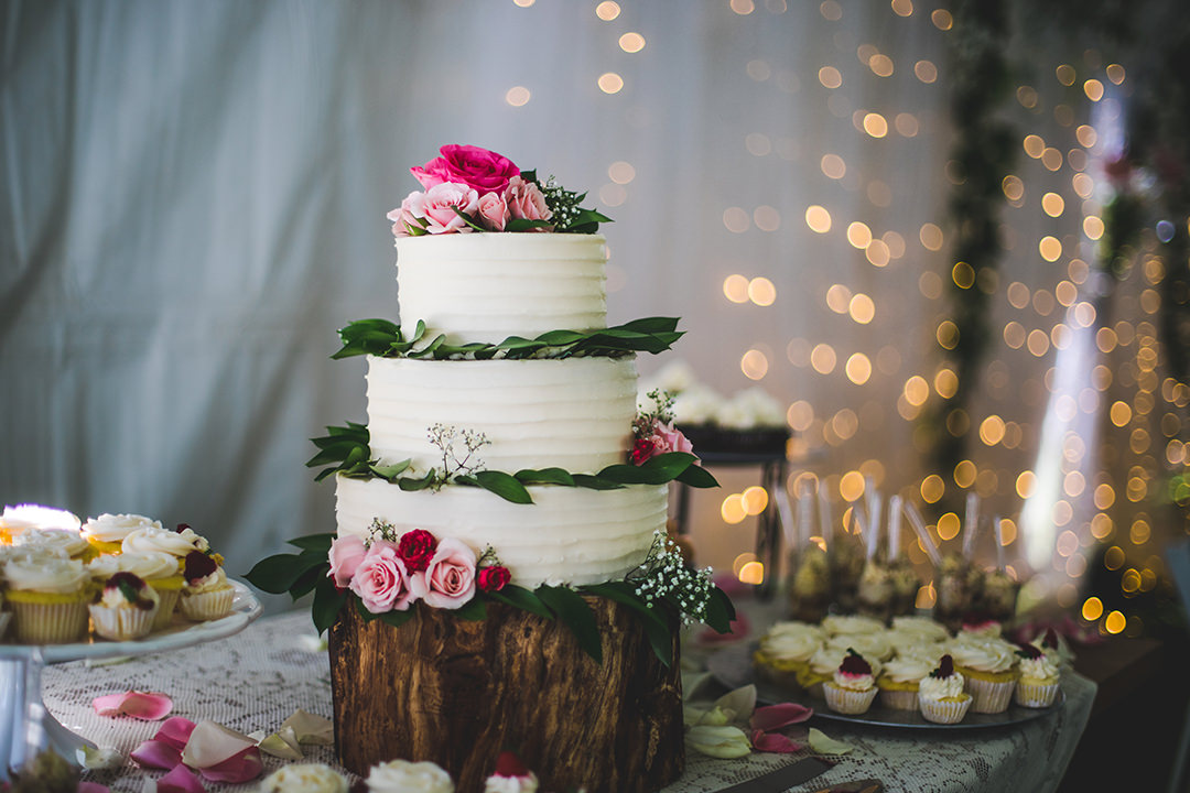 White wedding cake with flowers and greenery displayed with lights in background