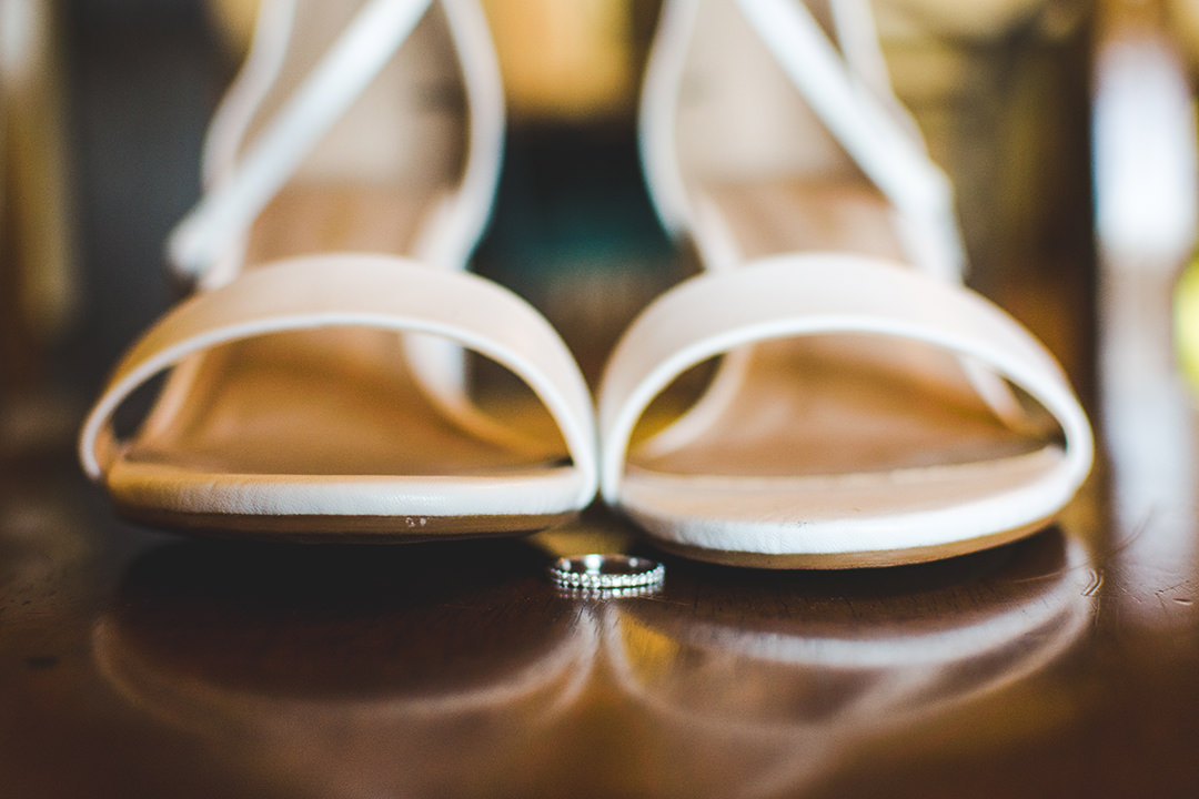 Wedding ring in front of the bride's wedding shoes