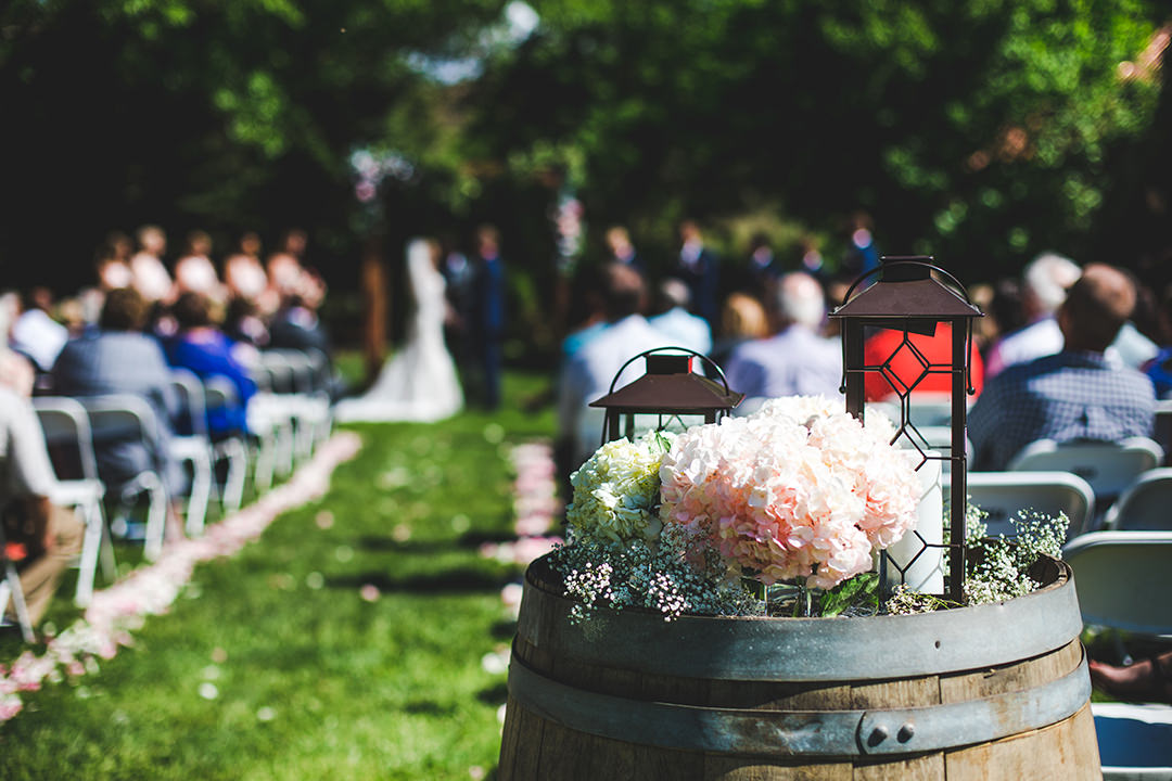 Detail shot of barrel with flowers with the wedding ceremony behind