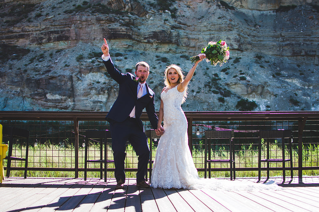 Groom and his bride jumping and celebrating their day while on a deck on the Gunnison River