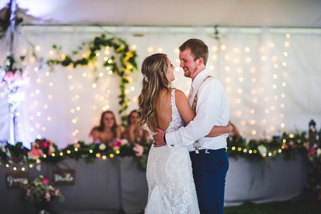 First dance with bride and groom in white tent with wedding party in background