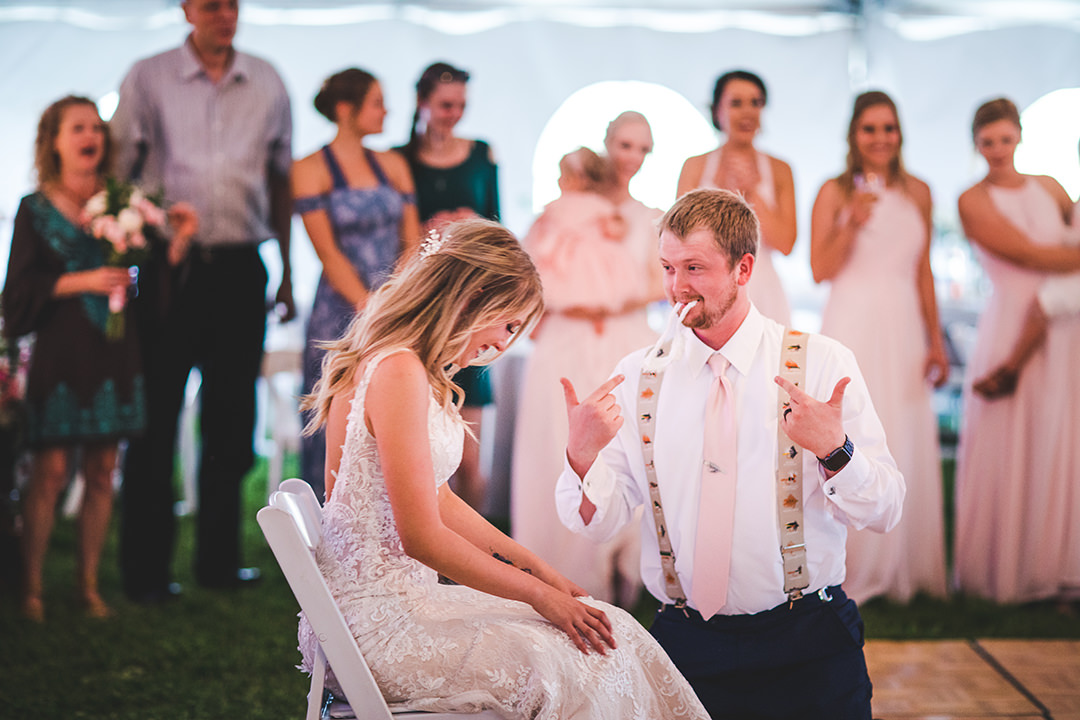Groom plays to the crowd after removing his hysterically laughing bride's garter