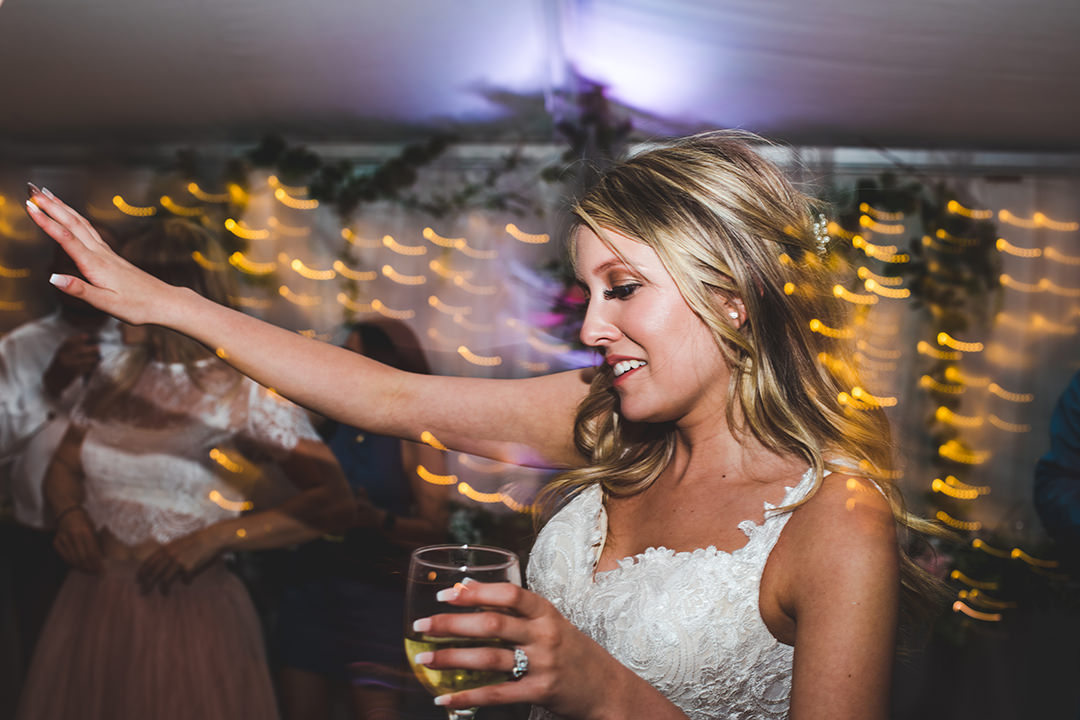 Partying bride with a shutter drag effect where lights are moving in background
