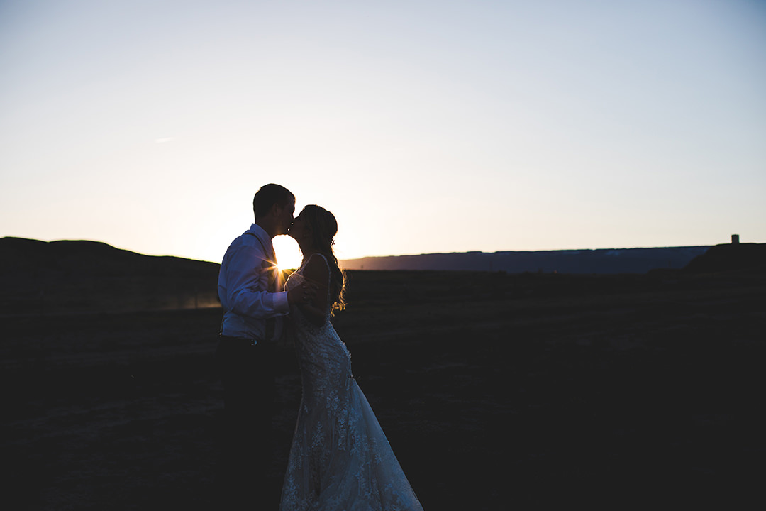 Married couple kissing while the sun sets behind them in Austin, Colorado
