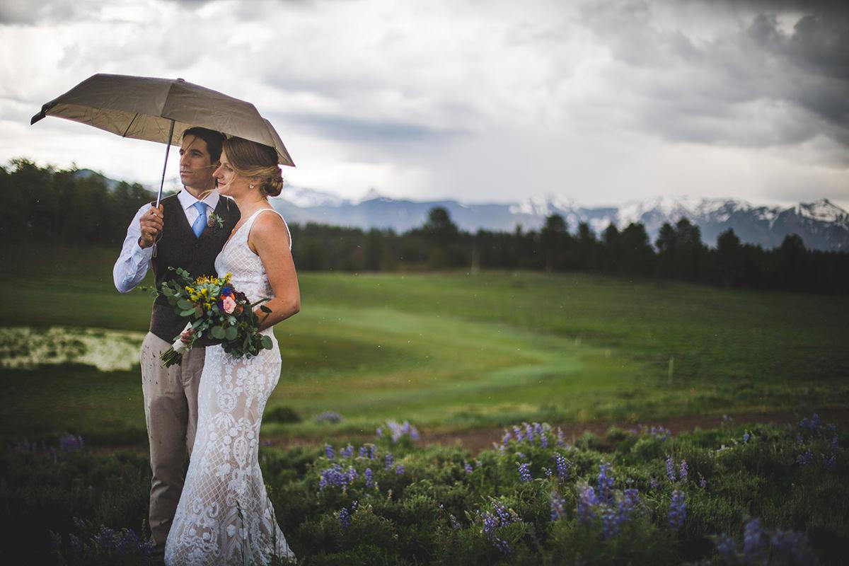 Groom and Bride under umbrella while rain sprinkles down