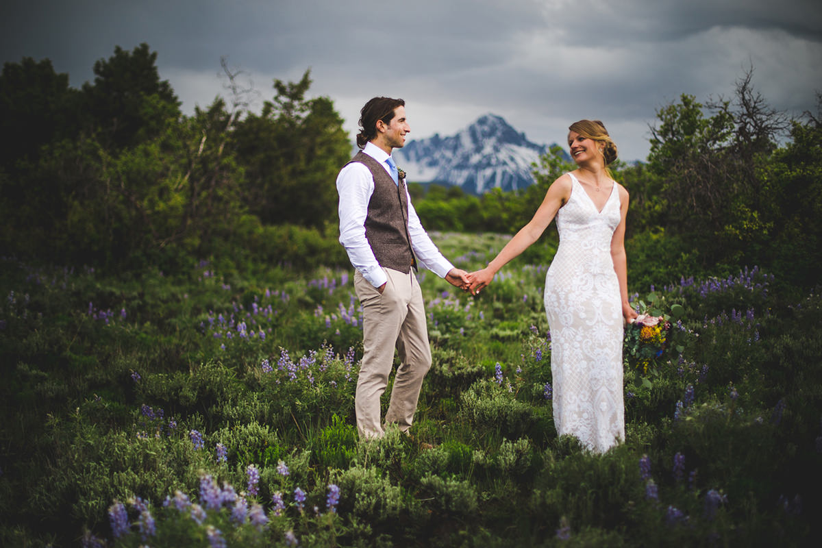 Bridal couple holding hands in lupine meadow at Top of the Pines