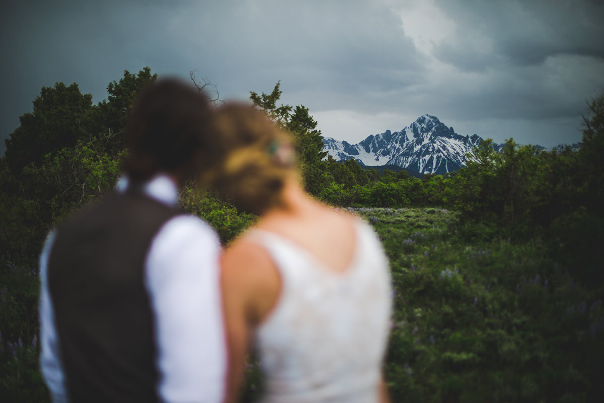 Bride and groom holding each other looking at Mount Sneffels