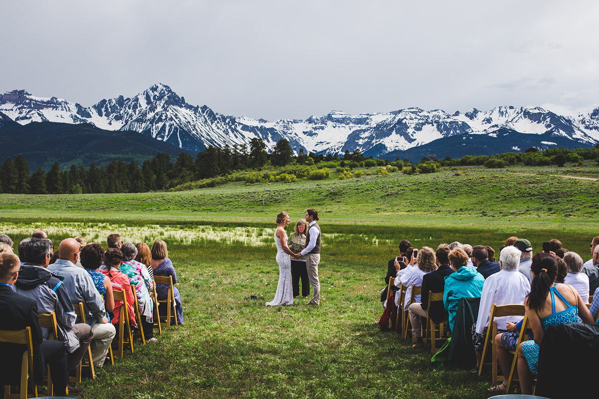 Ceremony at Top of the Pines with vibrant green meadow and San Juan Mountains in the background