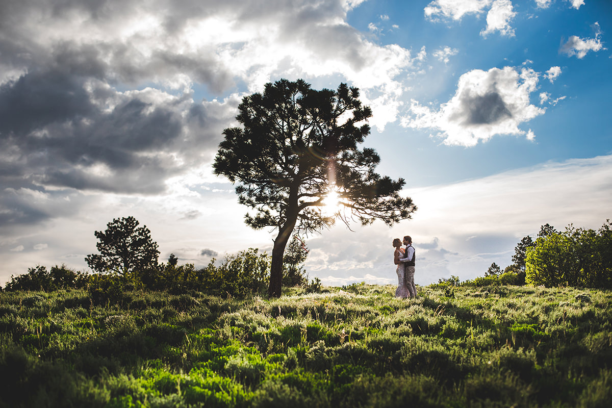 Silhouette of bride and groom with tree and sun behind them