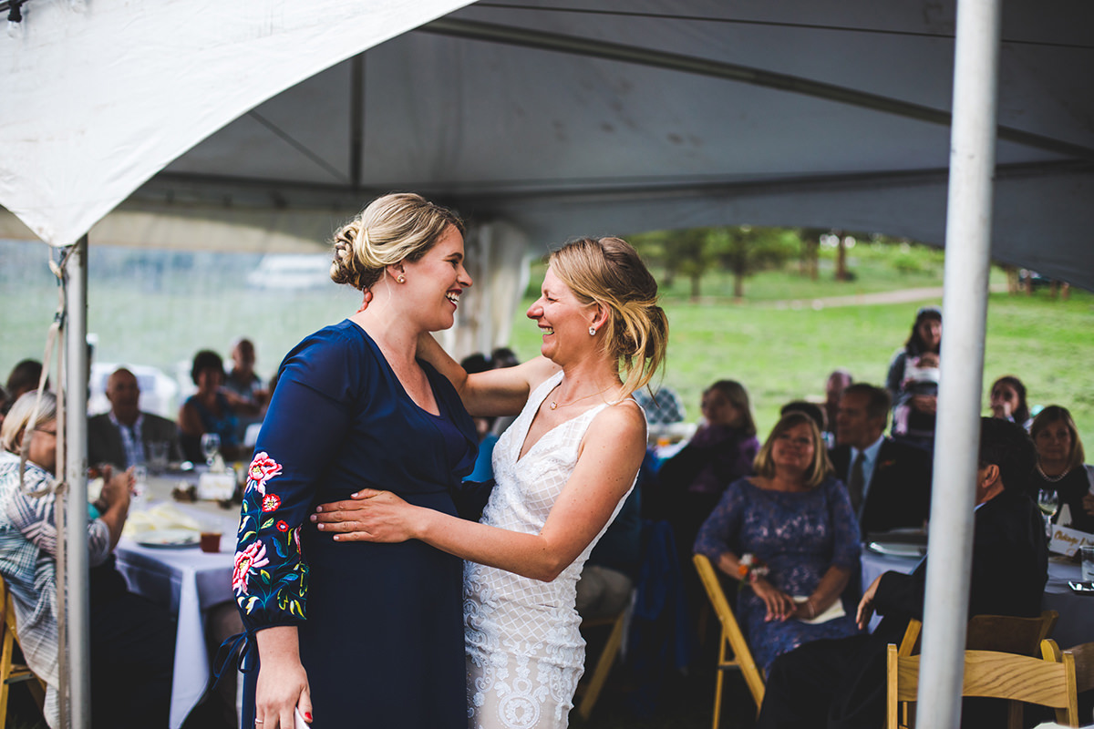 Bride laughing and crying with her sister after speeches