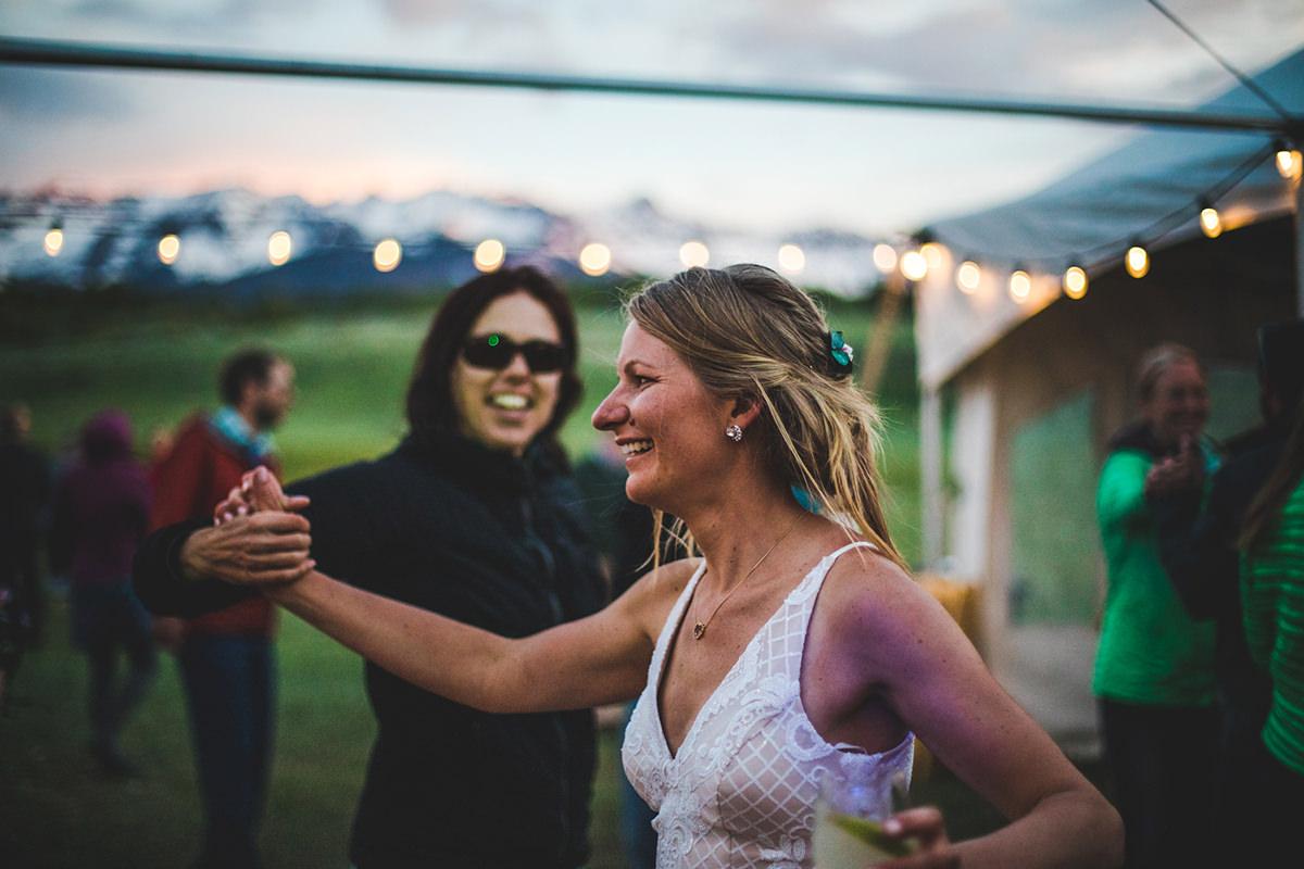 Bride dances with a friend while the sun sets