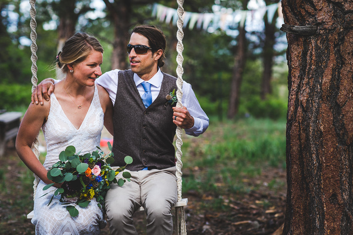 Married couple swinging on a swing in the woods