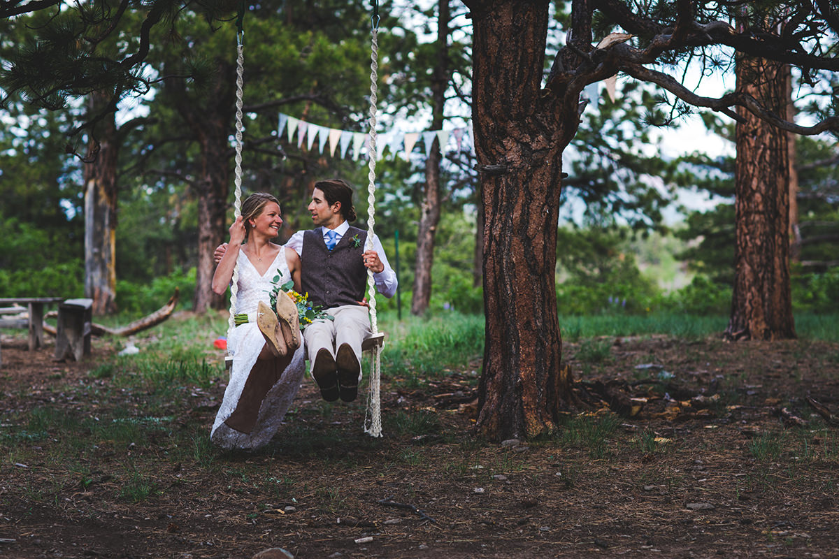 Smiling bride and groom swinging in the woods