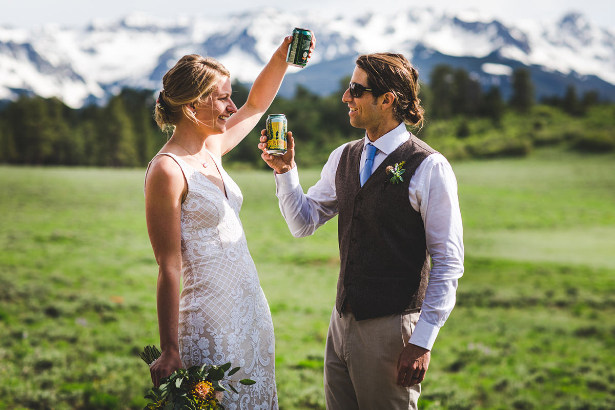 Couple clinking their beers after their wedding ceremony