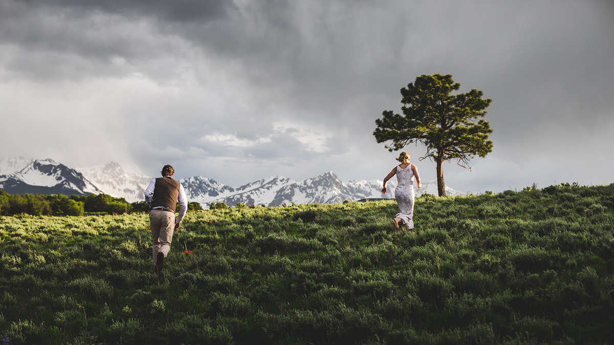 Groom runs after bride as she goes toward tree during sunset