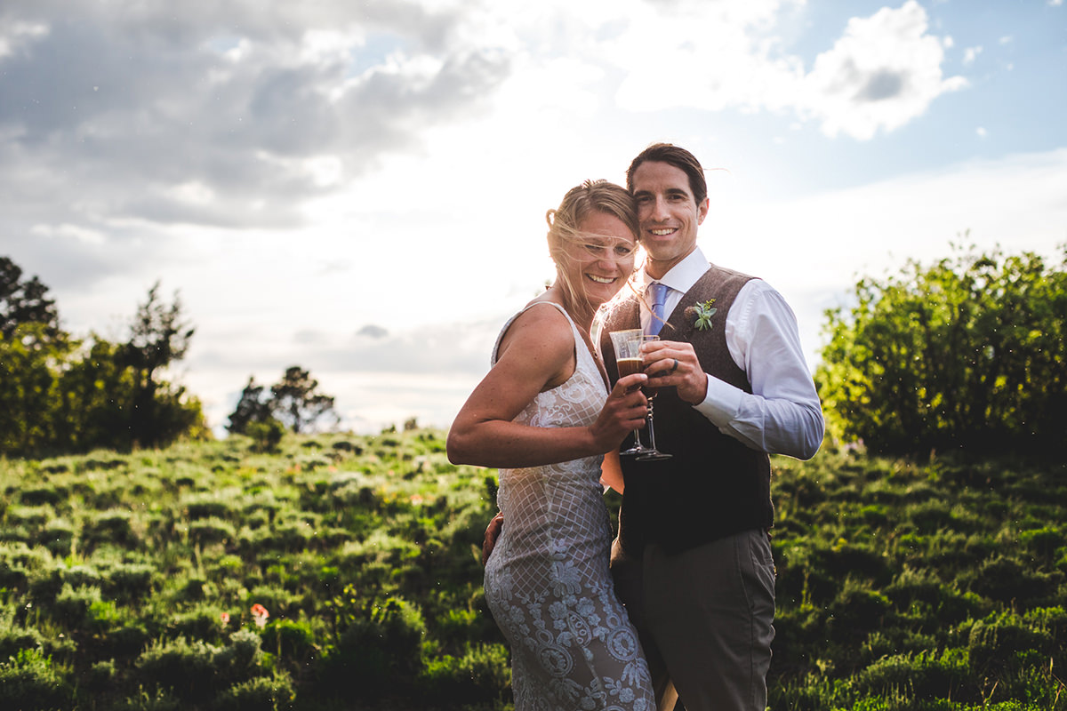 Bride and groom clinking glasses with sunset behind them