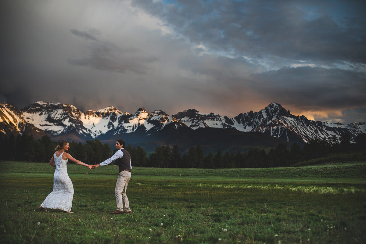 Just married couple dance in a meadow as sunset illuminates snow capped mountains