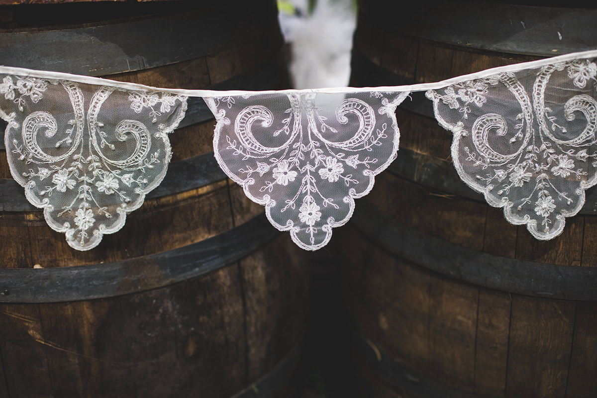 Lace adorning a wine barrel bar for wedding decorations