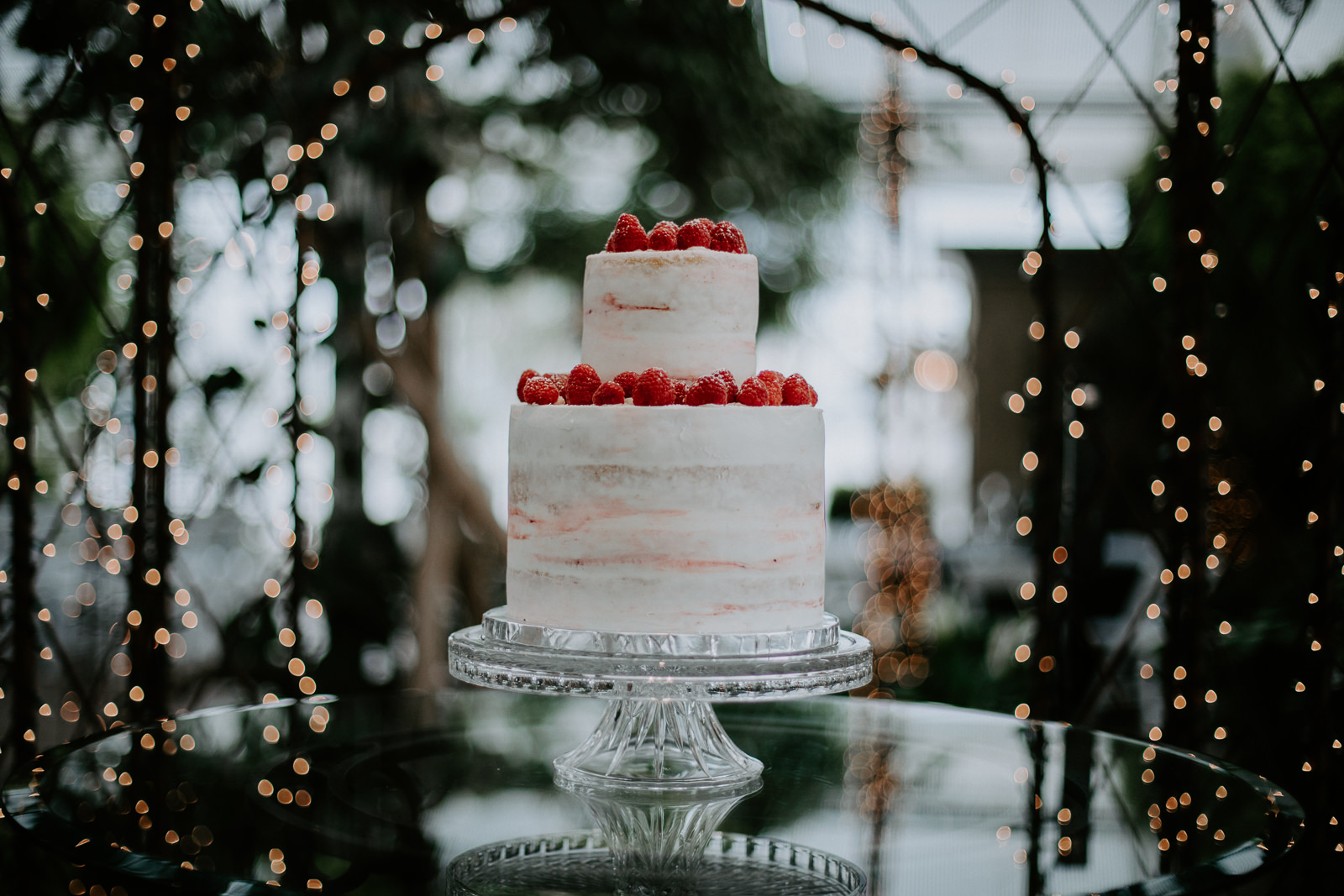 A white wedding cake adorned with raspberries on a glass table