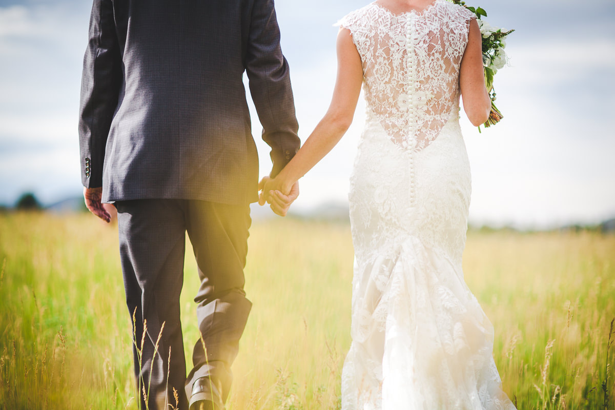 Bride and groom walking holding hands walking in a field away from the camera