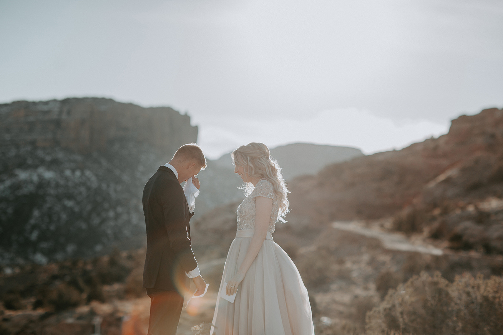Groom crying after seeing his bride for the first time with Colorado National Monument in the backdrop in Grand Junction