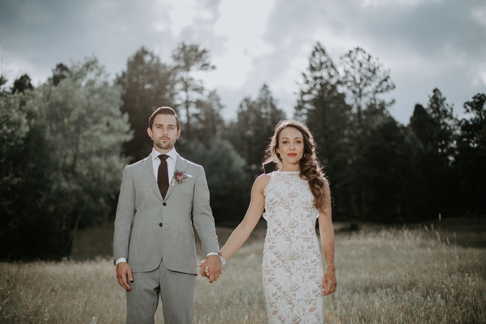 Couple holding hands on their wedding day looking straight at the camera with pine trees and clouds in background
