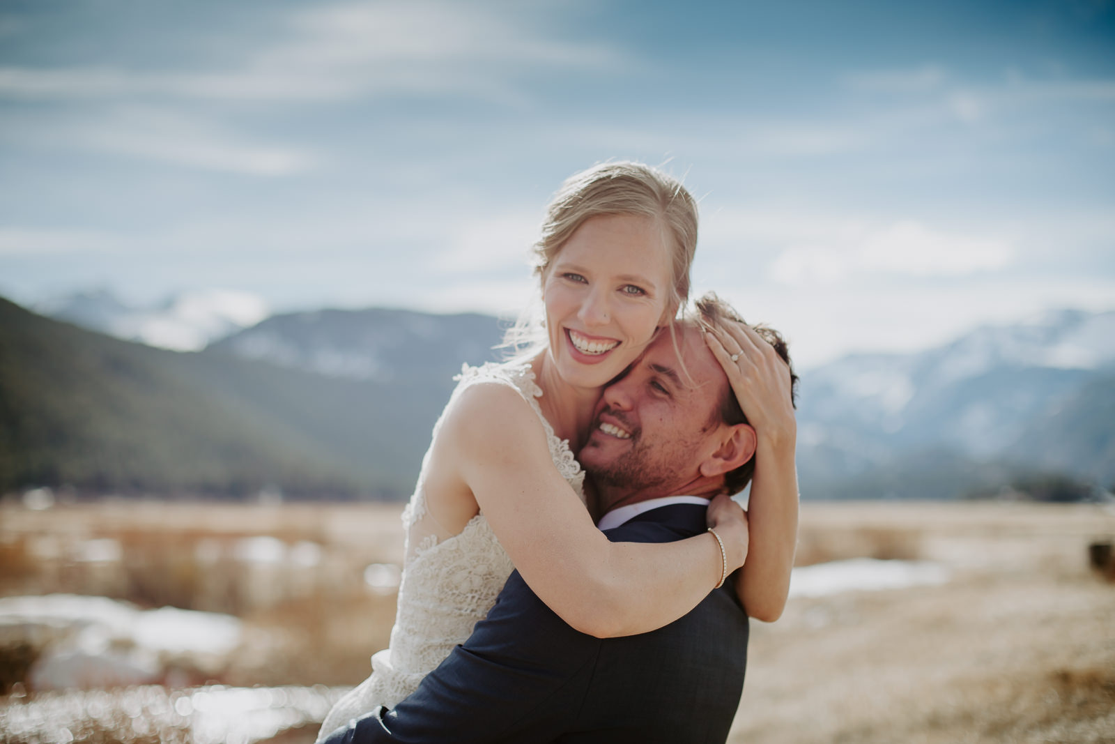 Bride hugs her groom up high around his neck and head in RMNP