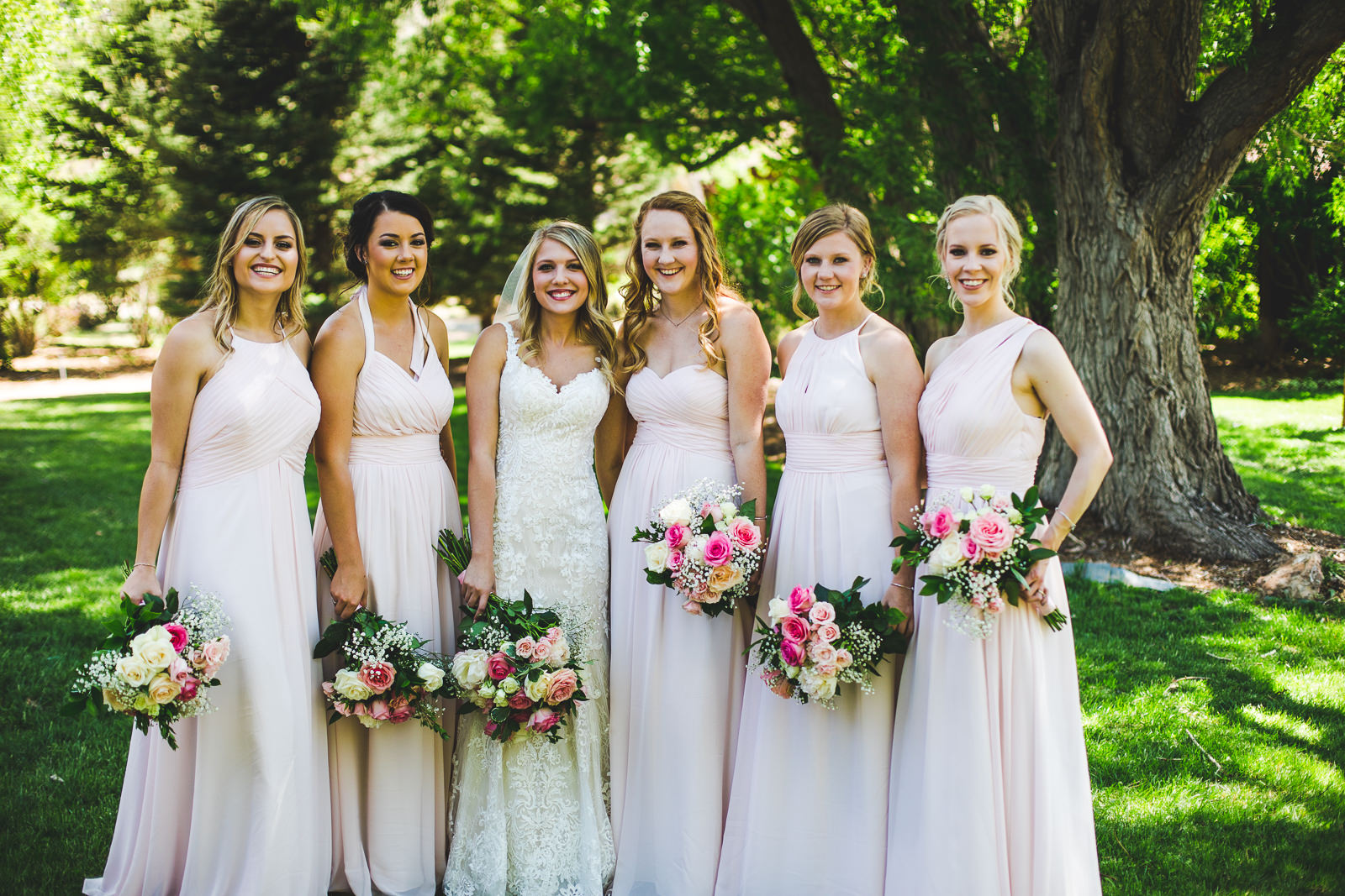 Bridal party in a group photo standing among trees