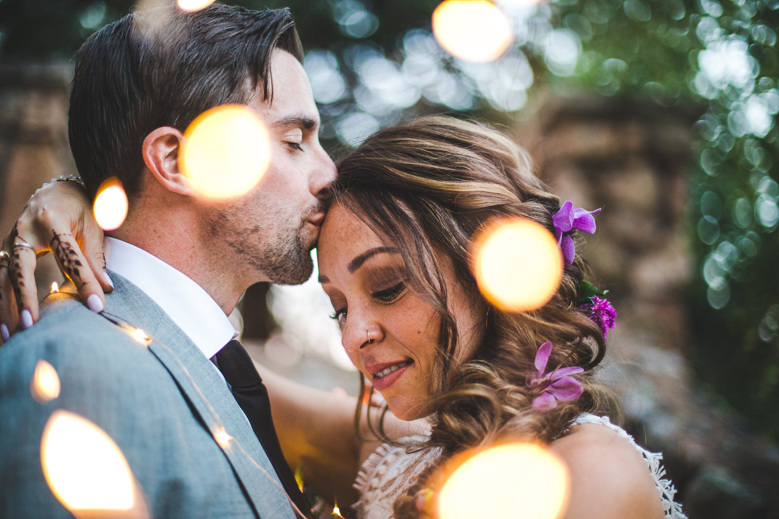 Groom kisses his bride on the forehead with small small white lights surrounding them