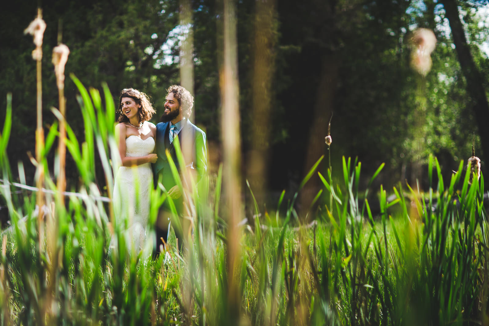 Peering through tall grasses at a wedding couple smiles looking at guests off camera