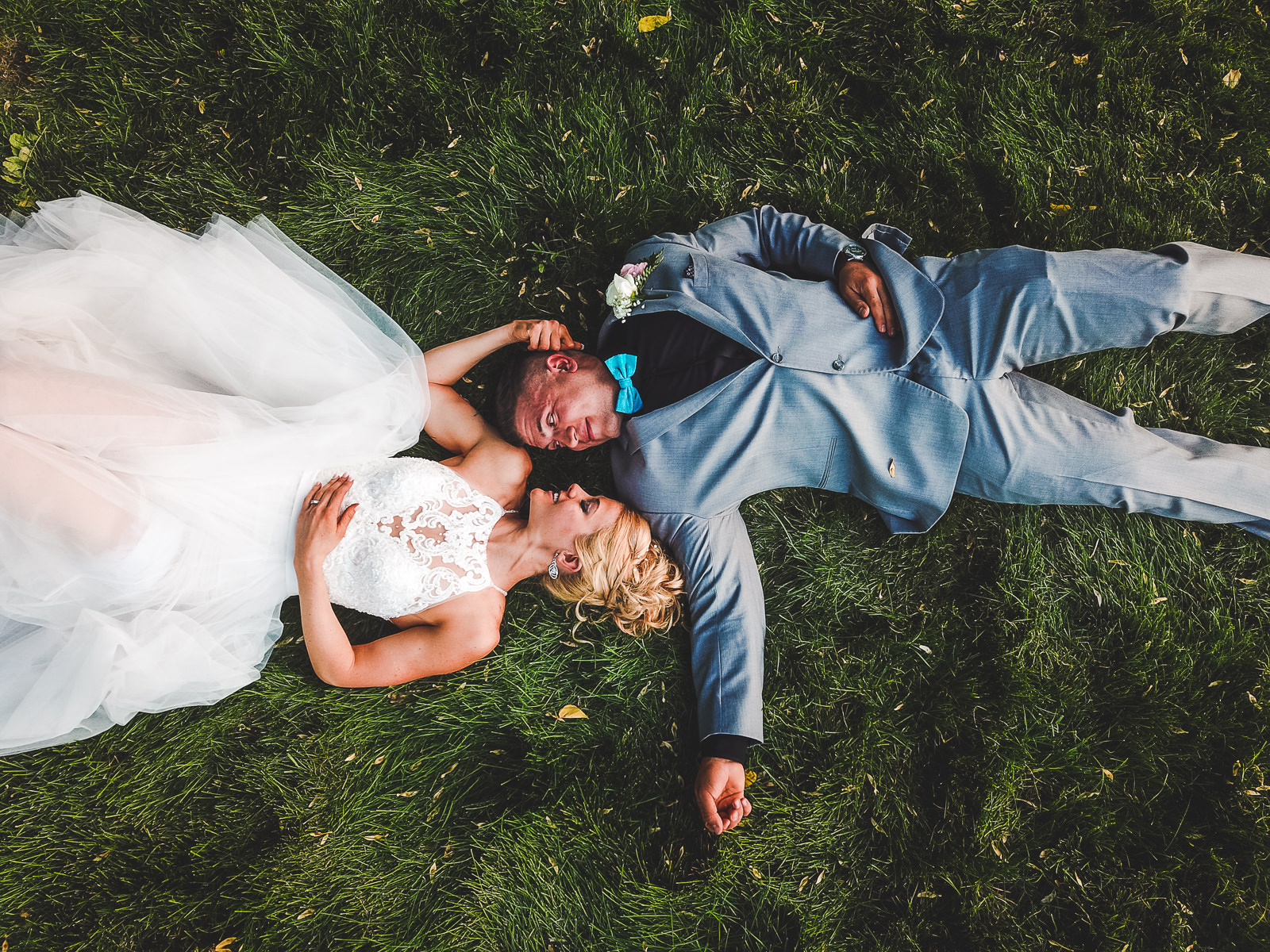 Bride in her white dress and groom in his gray suit lay in the grass smiling at each other