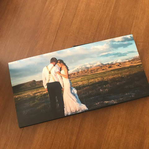 Photo of wedding album on desk with page open to bride and groom embracing in front of snow capped mountains and spring meadow