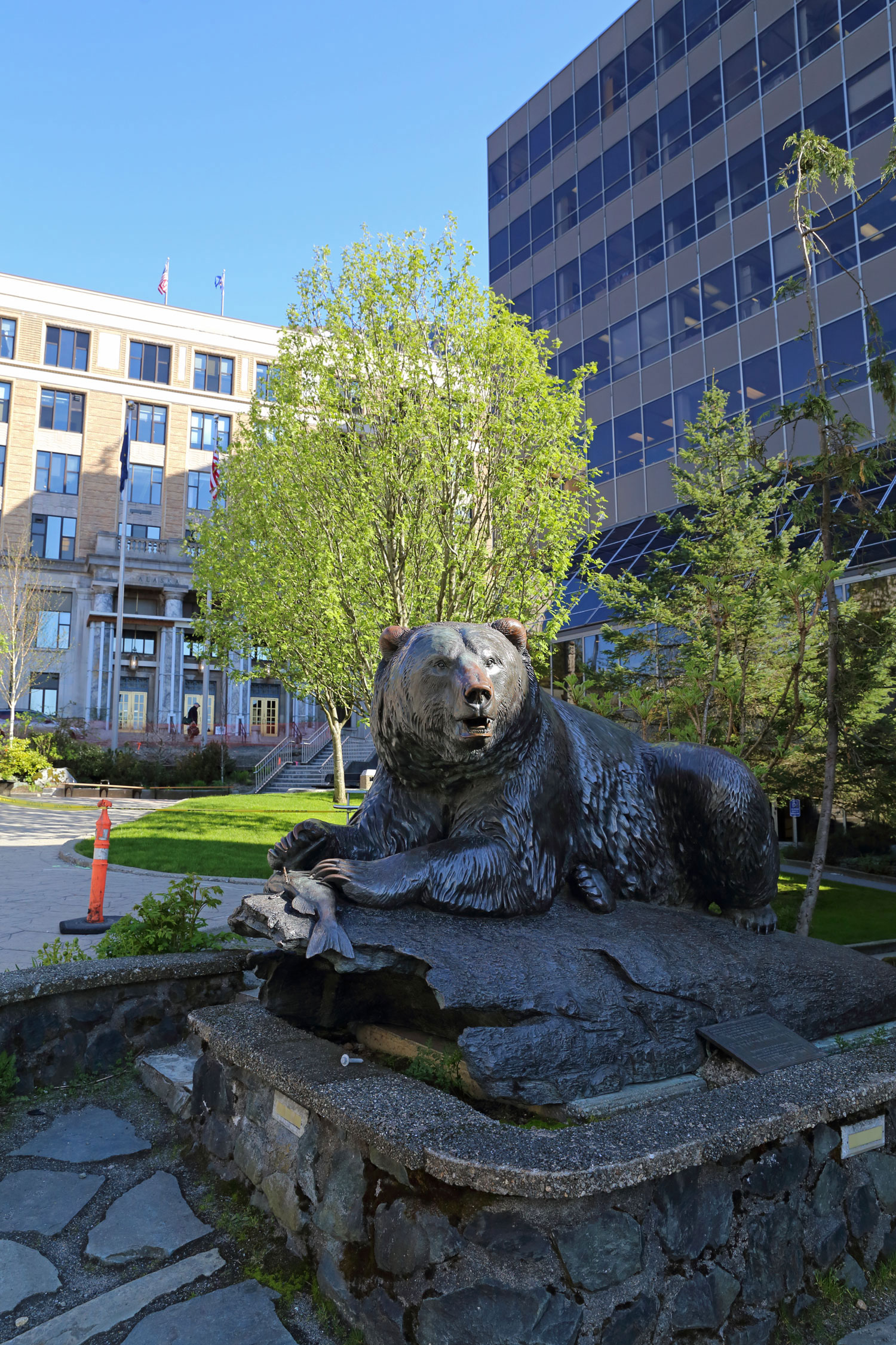 Windfall Fisherman, a bronze sculpture by R.T. Wallen of Juneau. The Alaska State Capitol Building is on the left and the Dimond Courthouse is on the right.