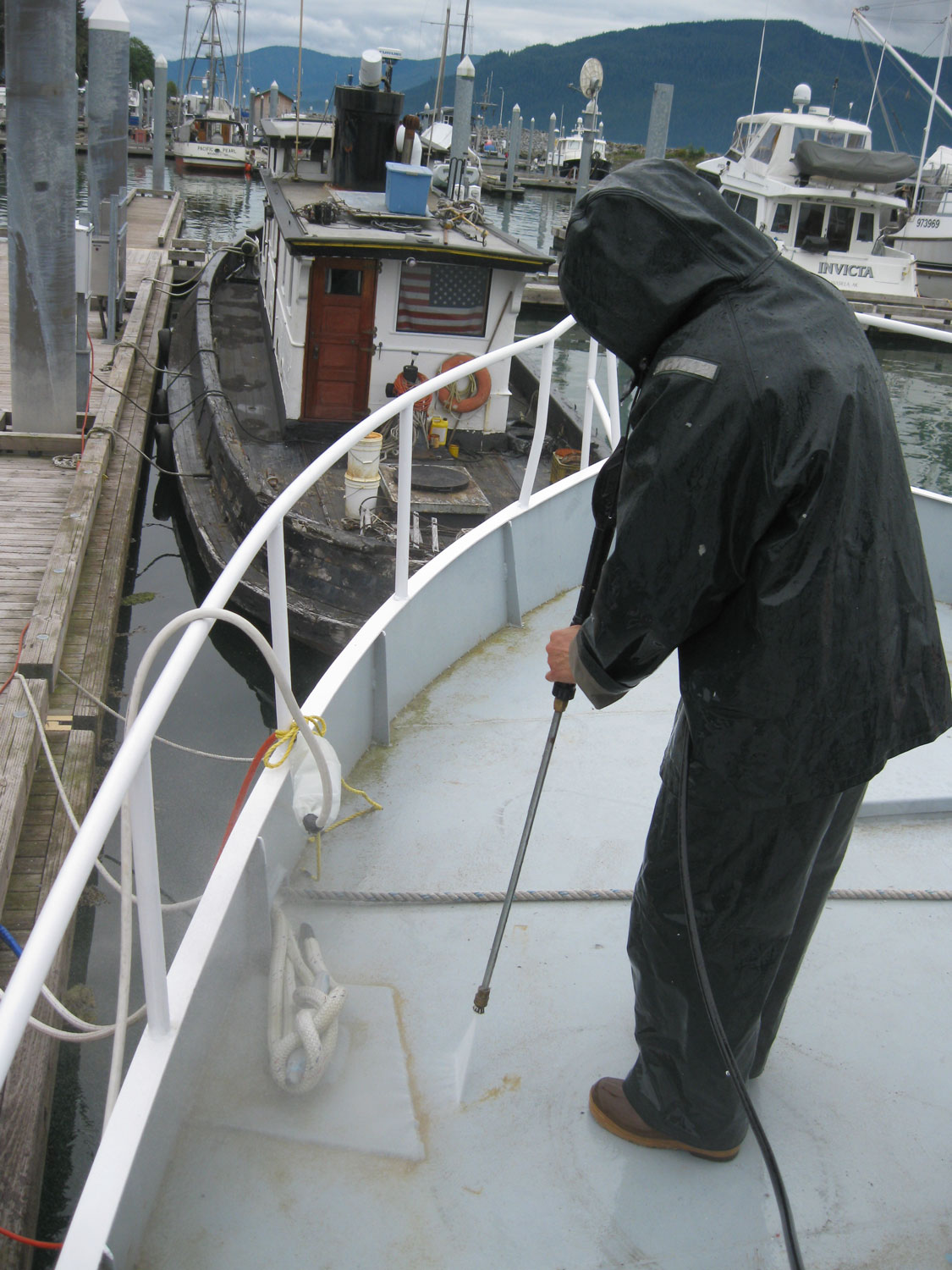 Pressure washing decks all decked out in raingear and safety glasses.
