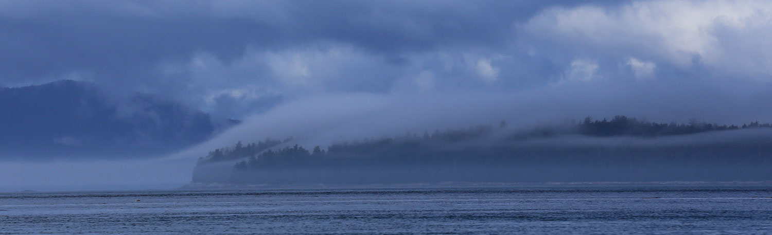 A marine layer slipping up over an island.