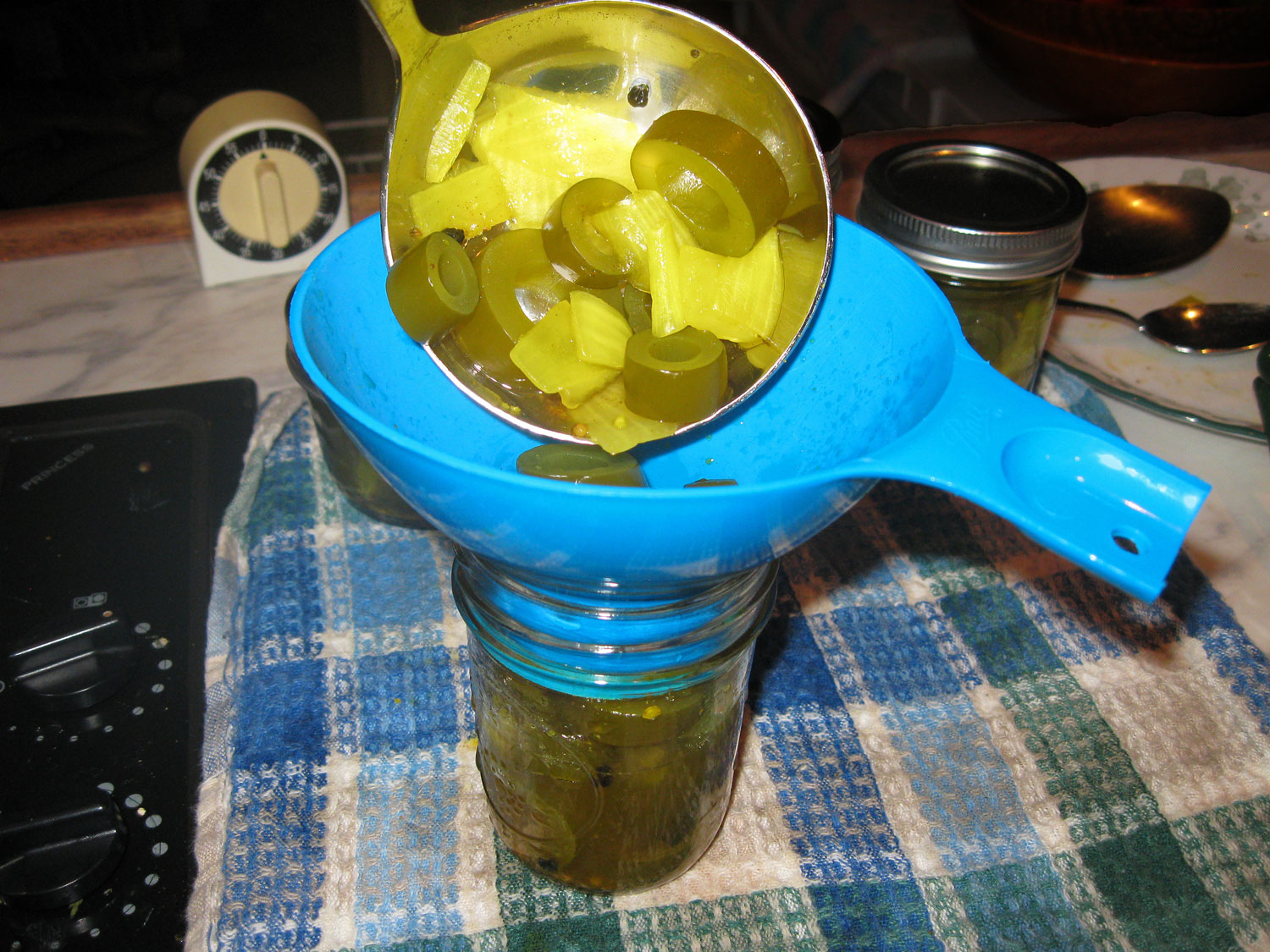 Ladling kelp pickles into the jar.