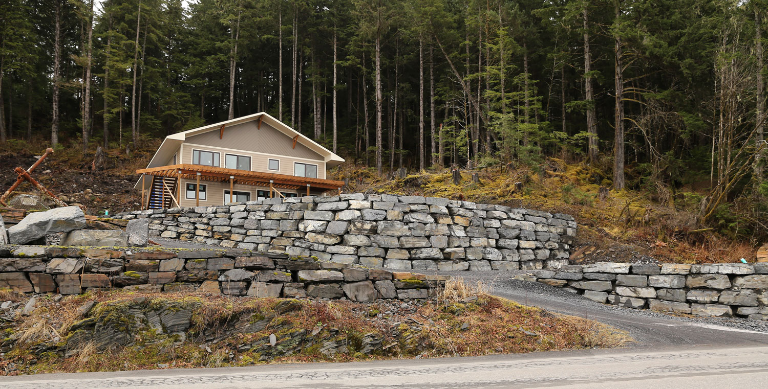 A new home built on a terrace with a stackwall, or stone retaining wall. The contractor compensated for the slope of the terrain and curved the wall around a corner.