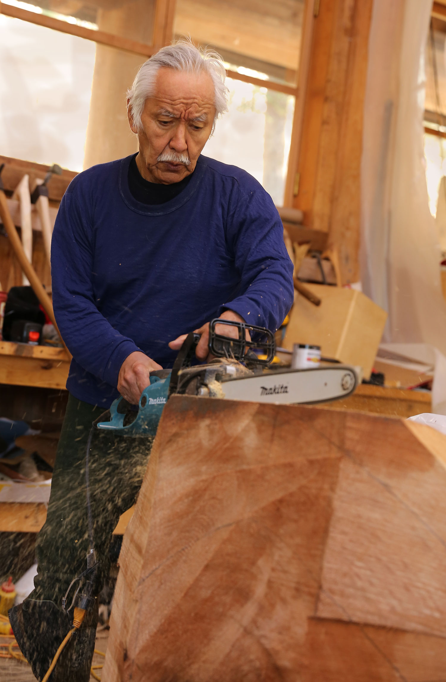 Nathan Jackson makes some initial cuts in a cedar log.