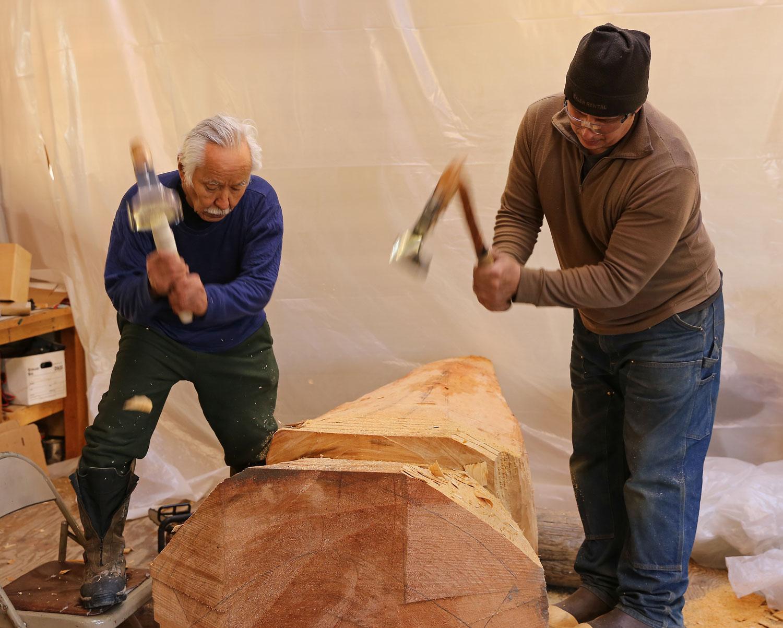 Nathan Jackson and John Hughes using adzes to shape a cedar log into a totemic sculpture.