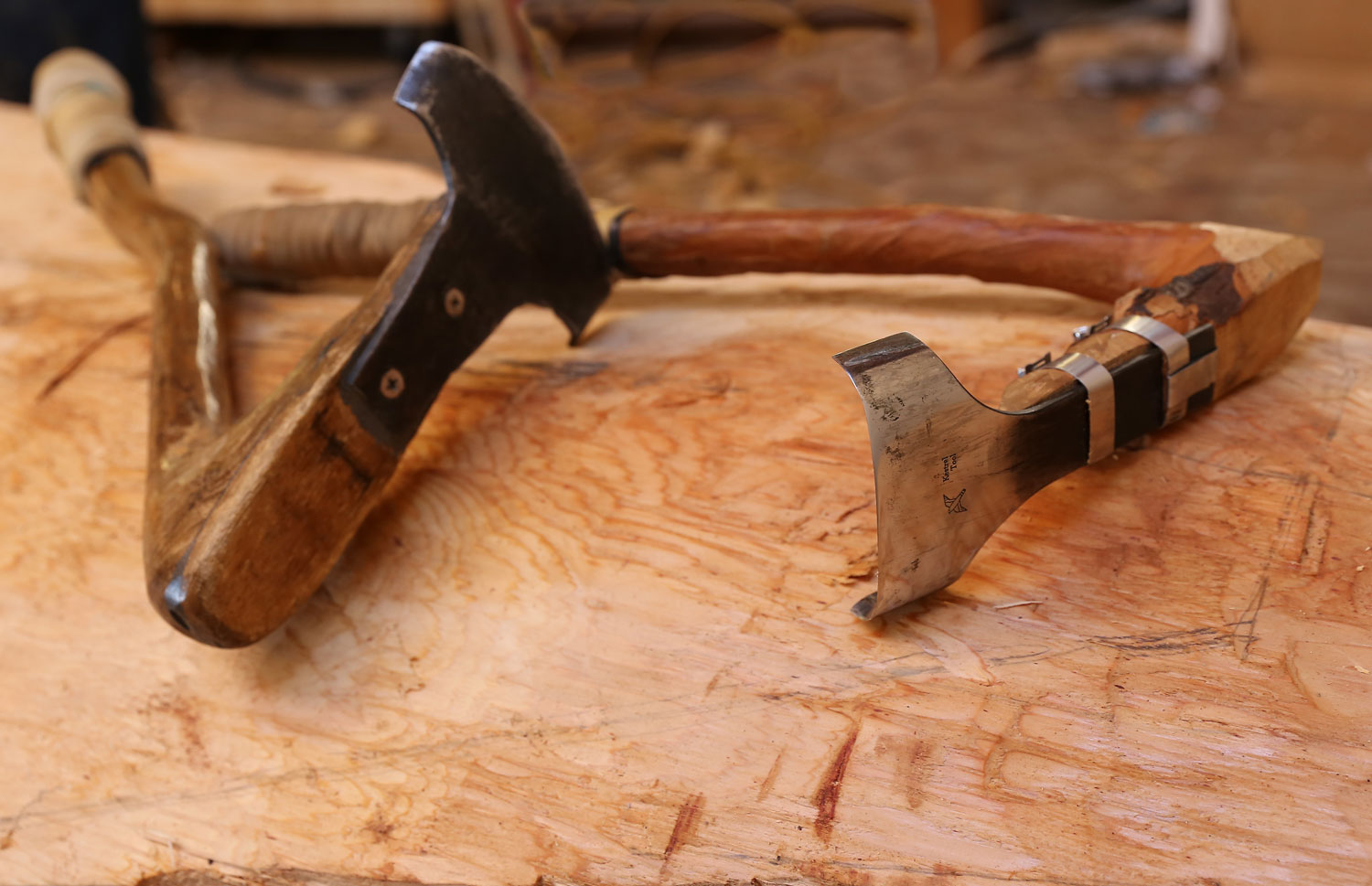 The adze head is attached to a handle made from a natural bend in an alder.