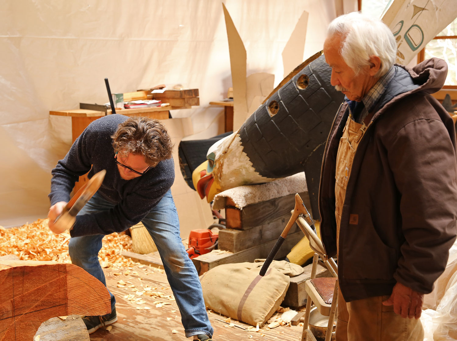"""Donald Varnell uses an adze to refine a form as Nathan Jackson watches. They are reproducing the eagle carving """"Thundering Wings"""" in the background. The eagle's wings were removed to transport it to the carving shed."""