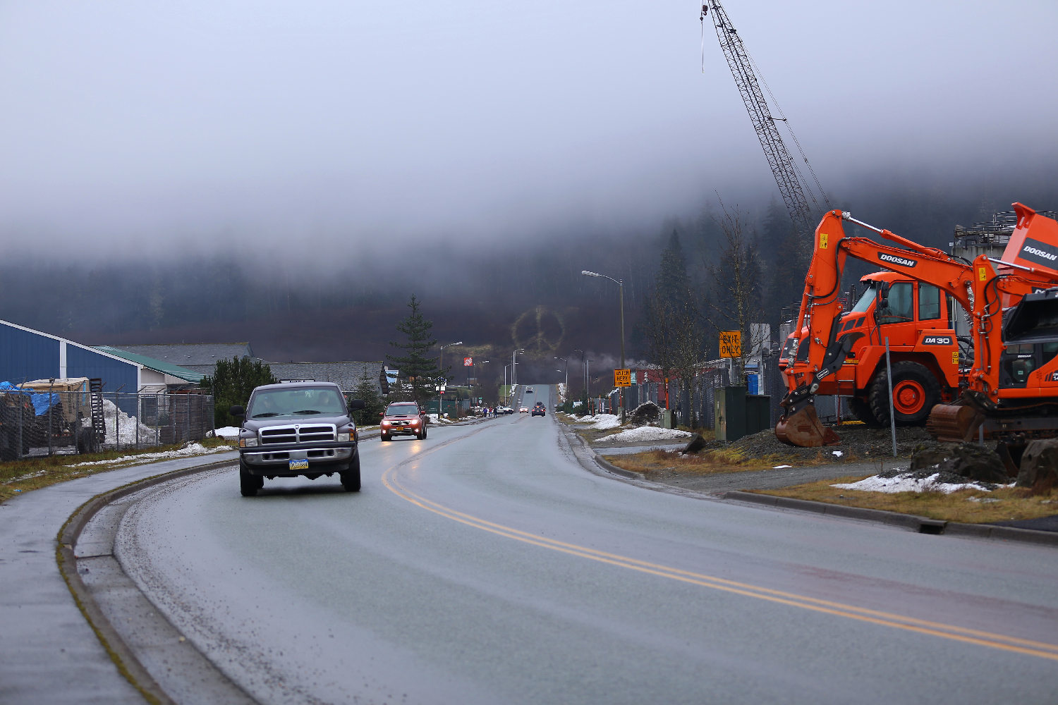 Peace sign Juneau Alaska Commercial Boulevard blvd construction equipment traffic road snow fog hillside