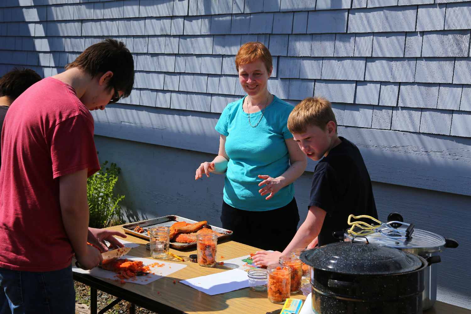 Josh and Ben cut up smoked salmon with Sarah. She is with the UAF Extension service and was in Hollis for the day teaching about safe and healthy food preservation.
